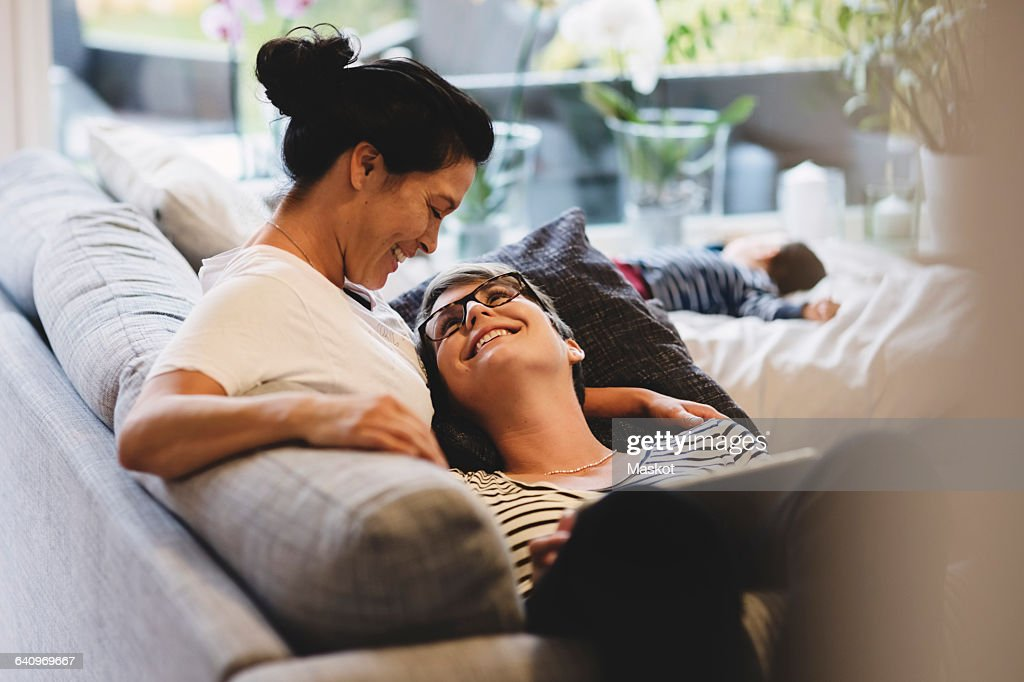 Smiling Lesbian Couple Embracing While Baby Girl Sleeping In Living Room At Home Stock -8376