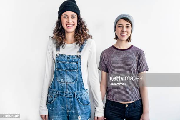 Smiling lesbian couple standing against white wall
