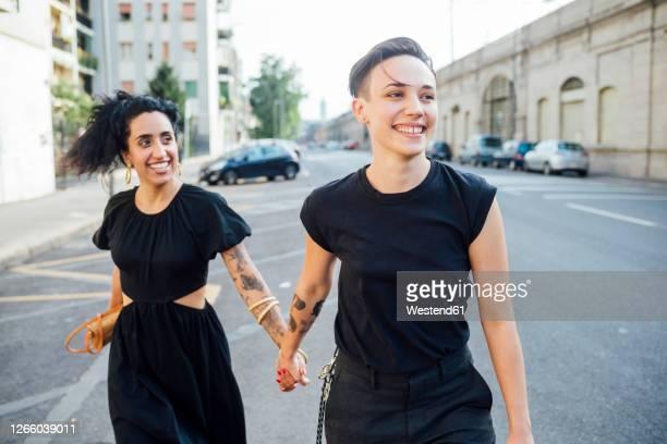 smiling lesbian couple walking in city - lesbisch lesbe lesben stock-fotos und bilder