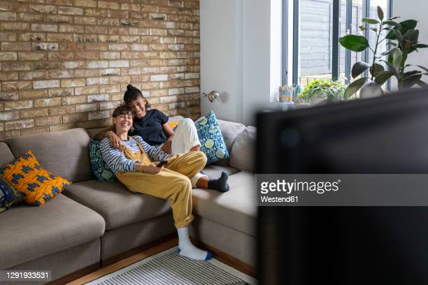 smiling lesbian couple watching television while sitting on sofa at home - television stock pictures, royalty-free photos & images