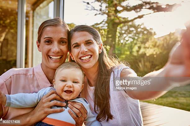 Smiling lesbian couple with baby on patio