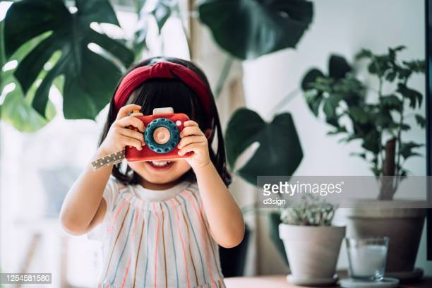 smiling little asian girl with red headband acting like a professional photographer having fun while taking photos with wooden toy camera in front of potted plants at home - photographe professionnel photos et images de collection