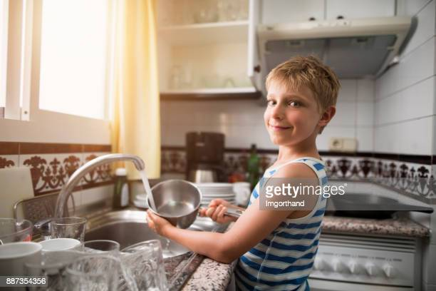 Smiling little boy cleaning dishes