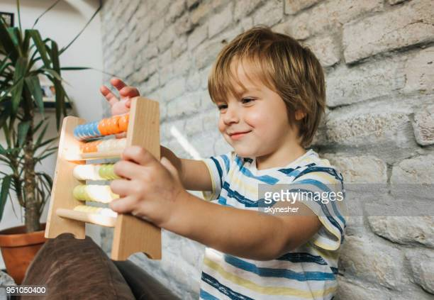smiling little boy counting on abacus at home. - fun calculator stock photos and pictures