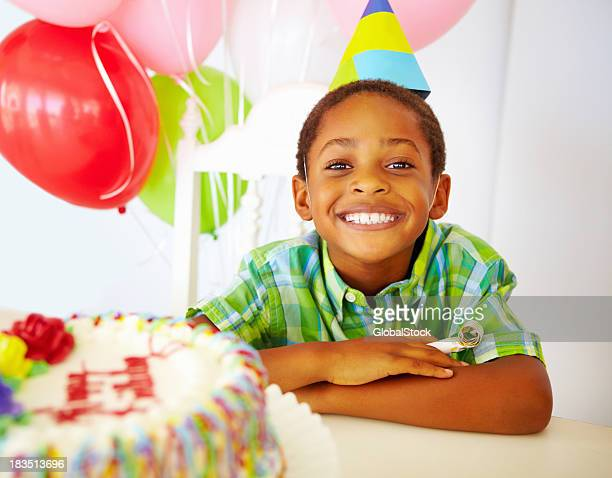 Smiling little boy in front of cake at birthday party