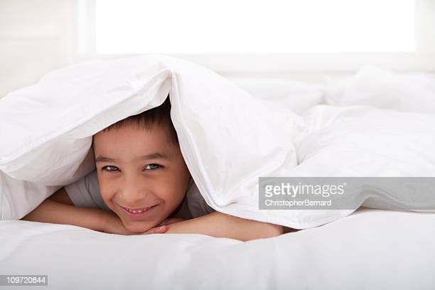 Smiling little boy laying under blanket