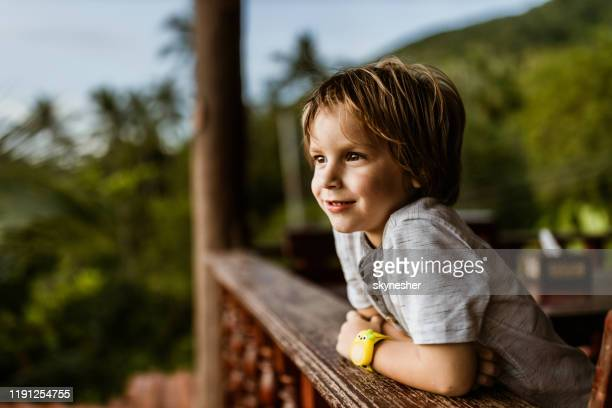 smiling little boy on a terrace. - only boys stock pictures, royalty-free photos & images