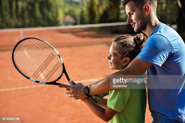 Smiling little boy practicing tennis with help of his coach.