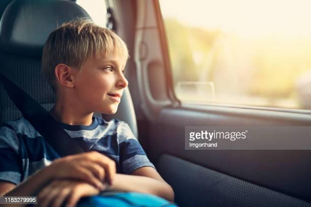 lächelnde kleine junge sitzt auto im kindersitz. - kind im grundschulalter stock-fotos und bilder