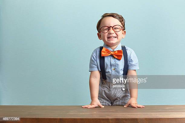 Smiling little boy sporting an orange bow tie and glasses