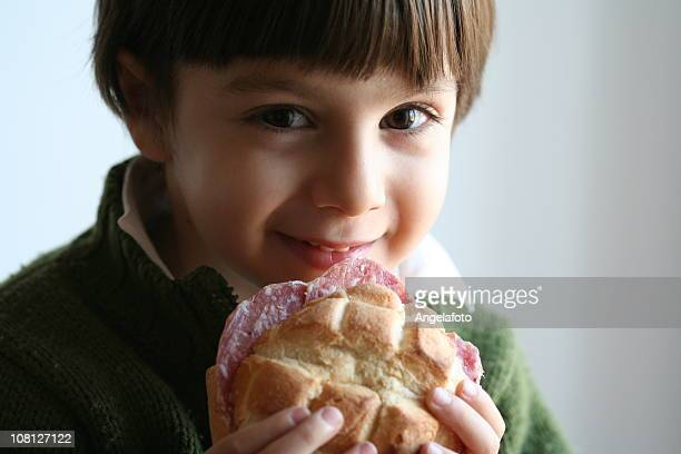 smiling little boy toddler eating salami sandwich on bun - sausage bap stock photos and pictures