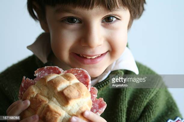 smiling little boy toddler eating salami sandwich on bun - pepperoni stock photos and pictures