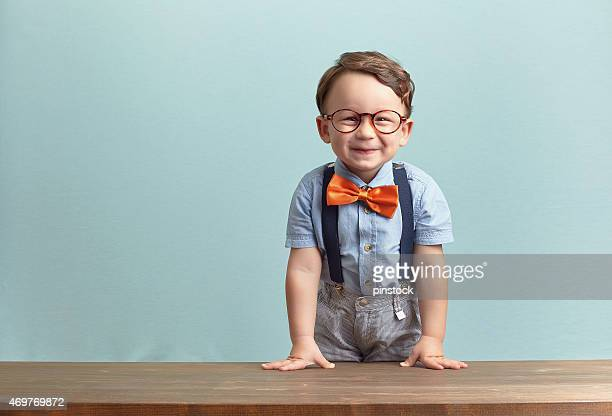 A smiling little boy wearing a orange bowtie and glasses