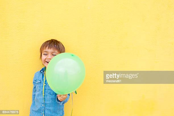 Smiling little boy with green balloon and streamer standing in front of yellow wall