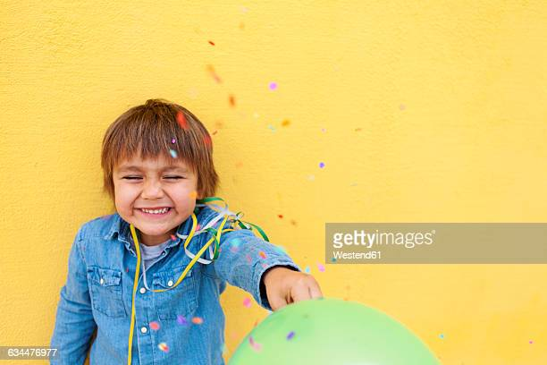 smiling little boy with green balloon, streamer standing in front of yellow wall while confetti falling down - alleen jongens stockfoto's en -beelden