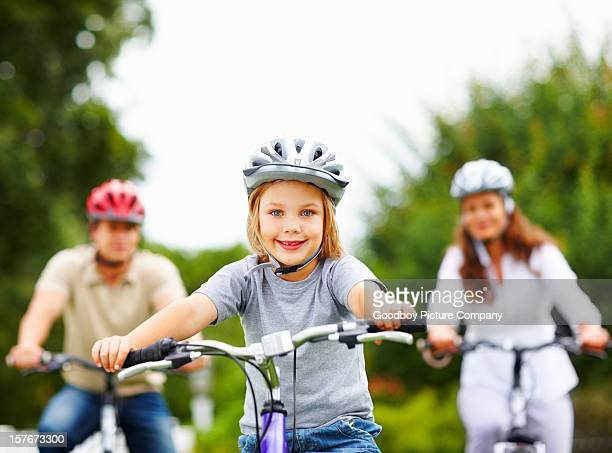 Smiling little boy with his parent in background riding bicycles