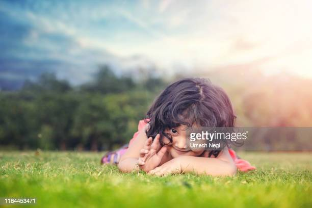 smiling little cute baby girl lying on the grass in the park - innocence stock pictures, royalty-free photos & images