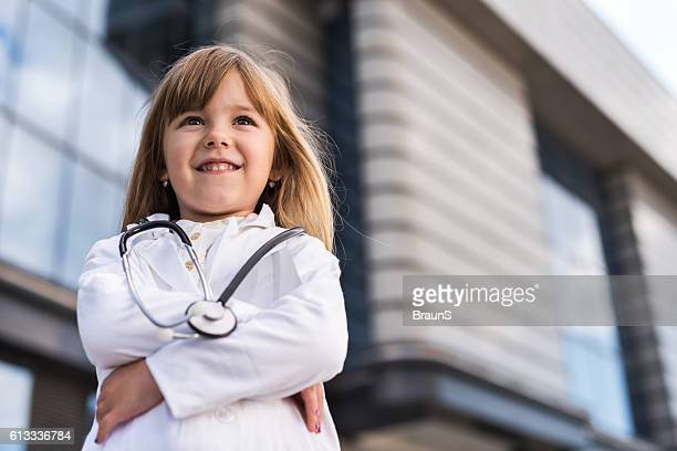 Smiling little doctor with her arms crossed outdoors.