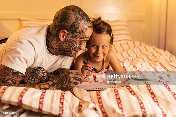 Smiling little girl and father coloring in the bedroom.