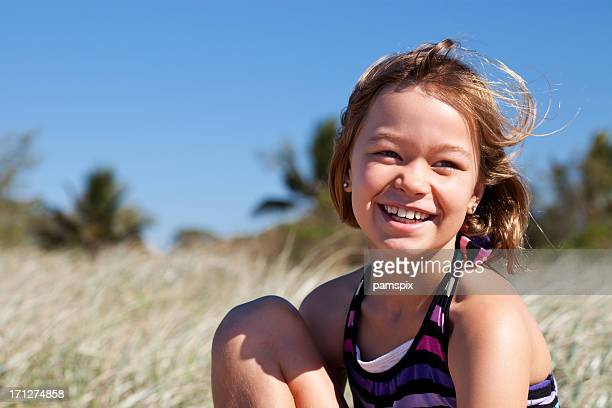 Smiling little girl at the beach with blue sky