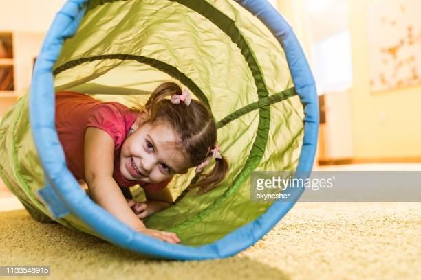 bambina sorridente che striscia fuori dal tubo del tunnel nella sala giochi. - solo bambini foto e immagini stock