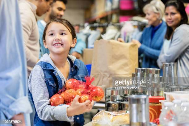 smiling little girl donates apples to food bank - community volunteer stock pictures, royalty-free photos & images