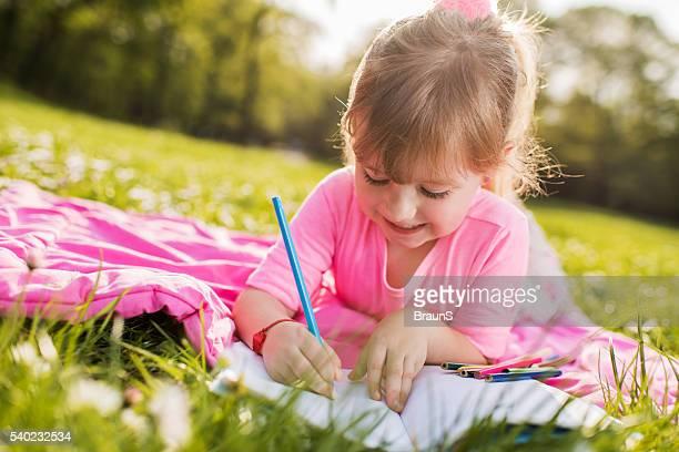 Sonriente niña pequeña dibujo durante la primavera día en la naturaleza.