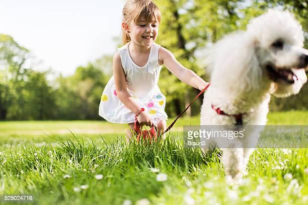 Fillette souriante profiter avec son chien dans le parc.