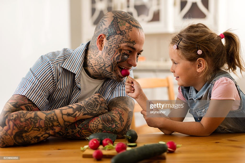 Smiling little girl feeding her father with a radish. : Stock Photo