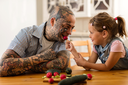 Smiling little girl feeding her father with a radish. 522850350