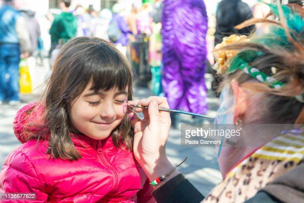smiling little girl getting her face painted by the face painter artist - traditional festival stock pictures, royalty-free photos & images