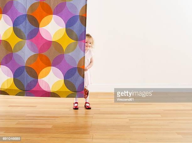 Smiling little girl hiding behind curtain
