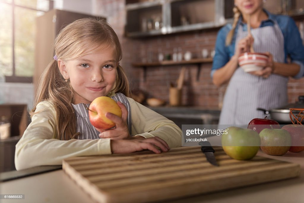 Smiling little girl holding apples in the kitchen : Stock Photo