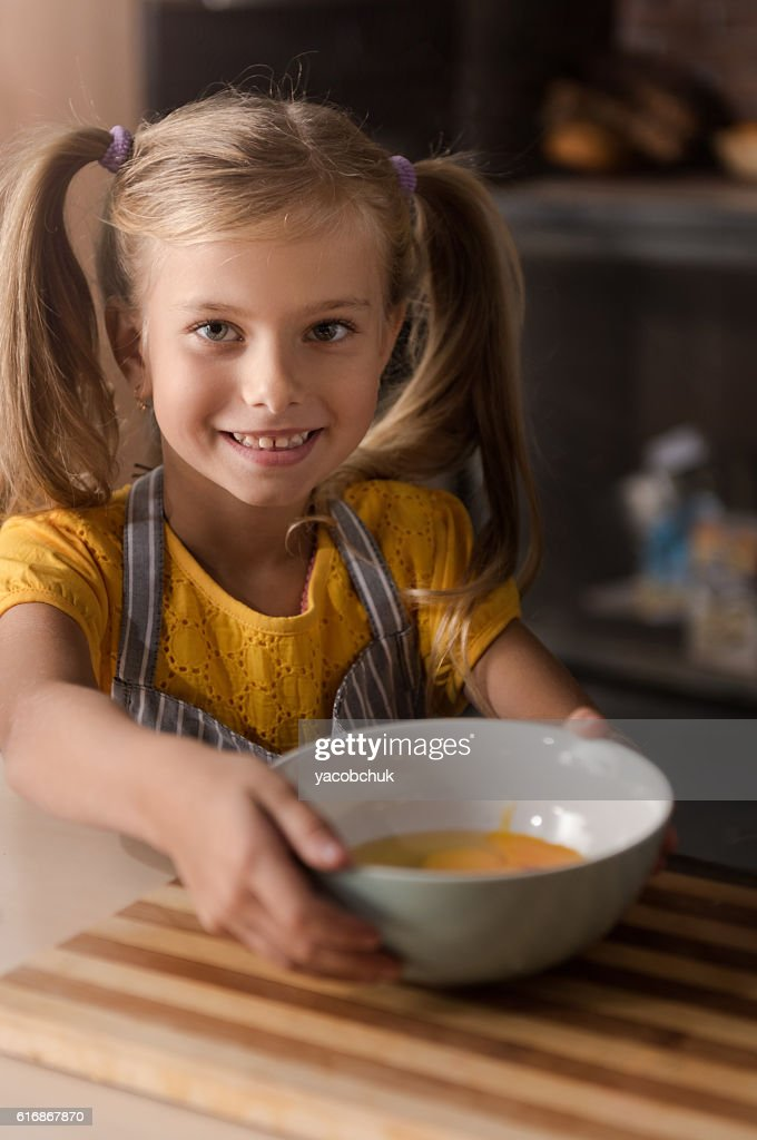Smiling little girl holding the bowl with broken eggs : Stock Photo