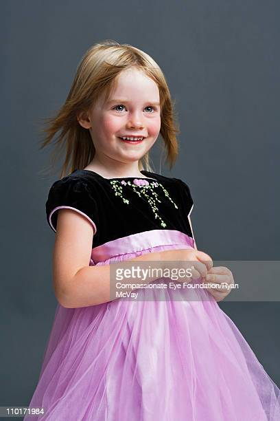 smiling little girl in a party dress - evening gown stock pictures, royalty-free photos & images