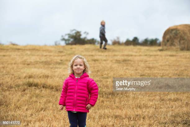 smiling little girl in pink jacket on a hayfield - ショッキングピンク ストックフォトと画像