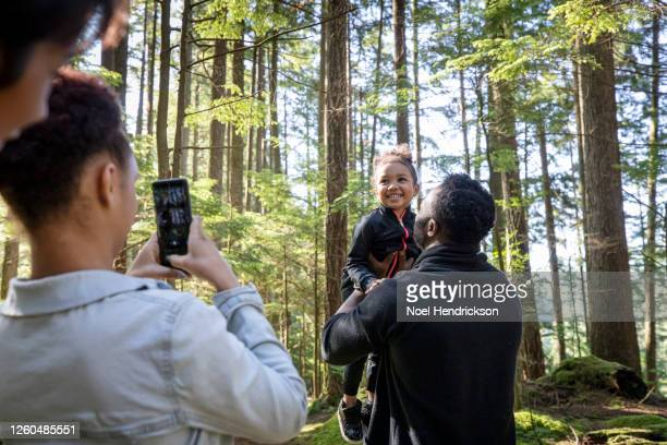 smiling little girl in the forest - travel stock pictures, royalty-free photos & images