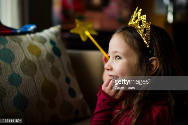 a smiling little girl in window light wears a golden crown and wand - principessa foto e immagini stock
