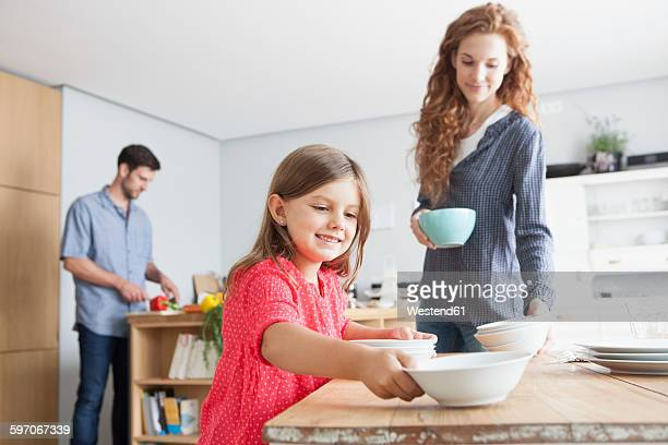 Smiling little girl laying the table in the kitchen with her parents in the background