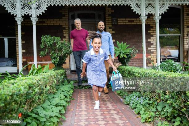 smiling little girl leaving house and running to school while fathers watching her -  lgbtqi ストックフォトと画像