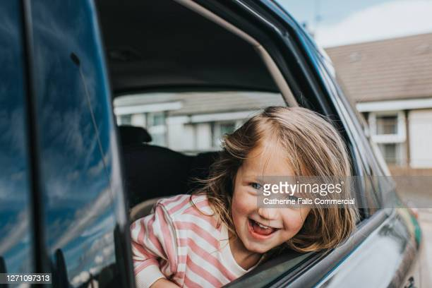 smiling little girl looking out of a car window - car stock pictures, royalty-free photos & images