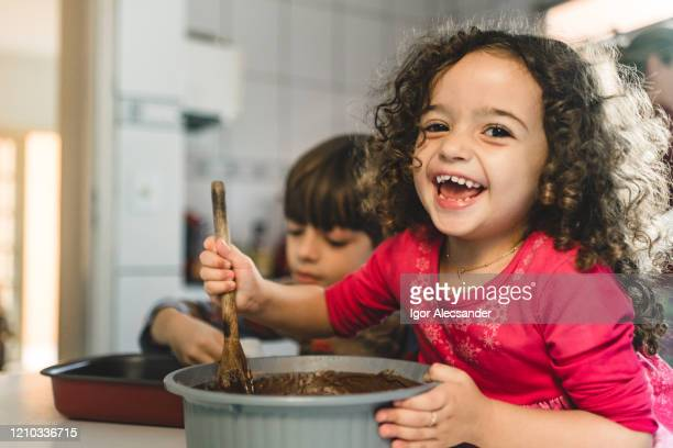 smiling little girl making cake - easter sunday stock pictures, royalty-free photos & images