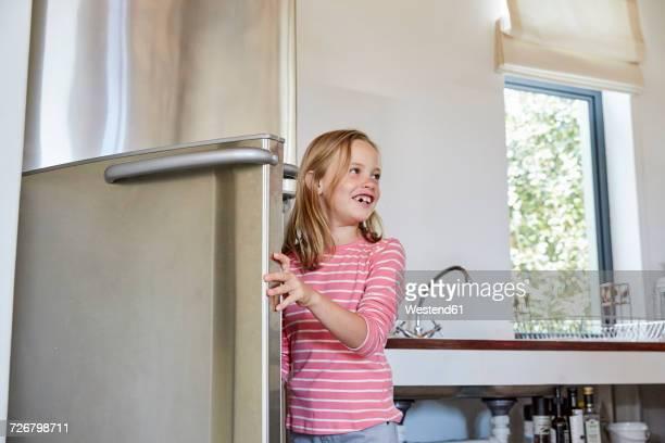 Smiling little girl opening fridge