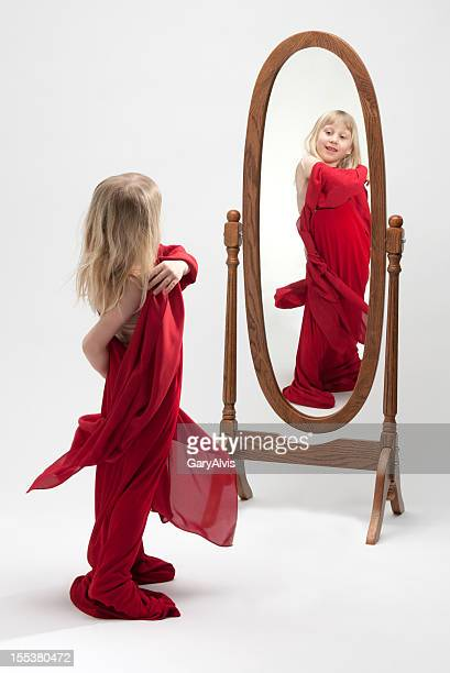 smiling little girl playing dress up-reflection in mirror - full length mirror stock photos and pictures