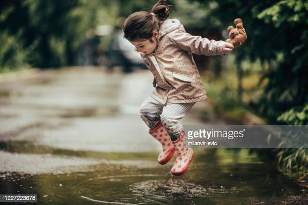 smiling little girl playing in a puddle stock photo - puddle stock pictures, royalty-free photos & images