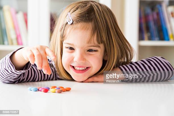 Smiling little girl playing with chocolate buttons