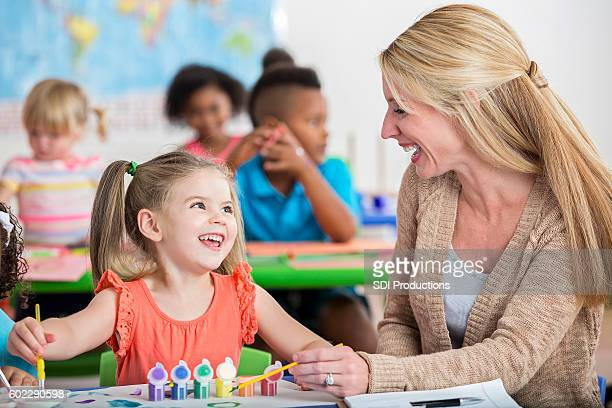 Smiling little girl playing with paints at daycare with teacher