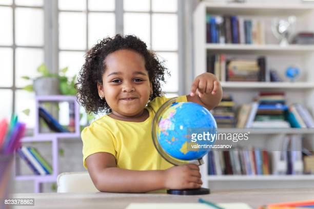 Sonriente niña señalando en lugar de un globo