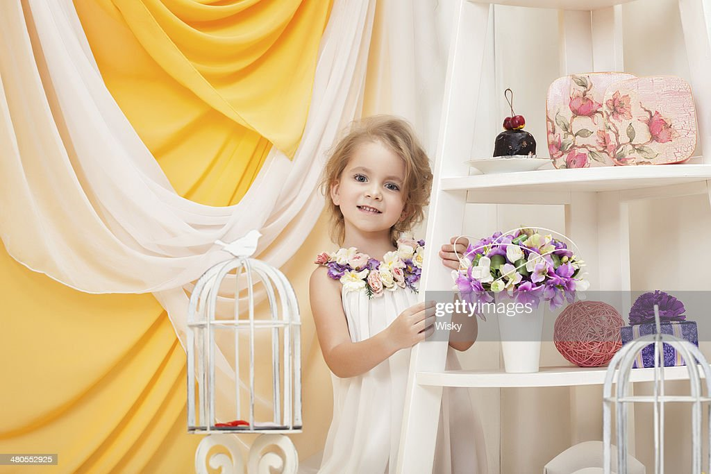 Smiling little girl posing in decorated studio : Stock Photo