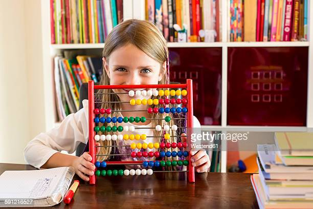Smiling little girl sitting behind abacus